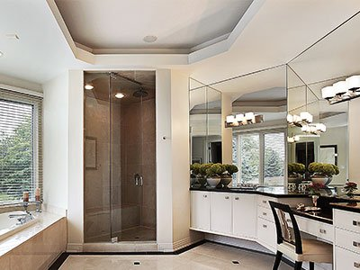 Average-sized bathroom with white cabinets, large mirrors, shower with glass door, large window, and modern lighting.