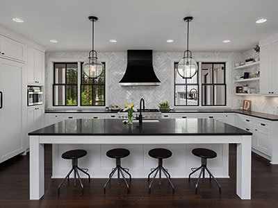 Average-sized kitchen with white cabinets, large island with balck countertop, four black bar chairs, and modern lighting.