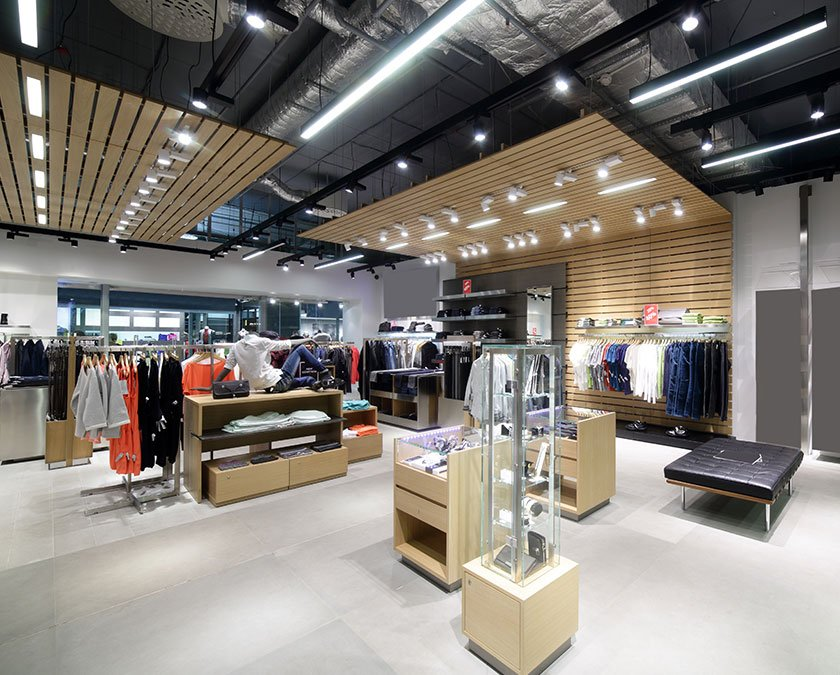 Interior view of a fashion store with light beige shelves, dark ceiling with LED lighting, white floor, and clothes on the shelves.