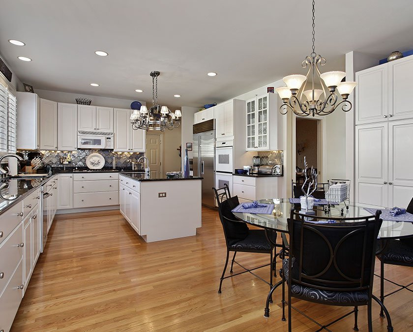 Modern kitchen with white cabinets, laminate floor, large island, quartz countertop, and table with black chairs.