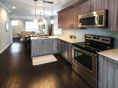 Small, modern kitchen with striped gray cabinets, composite floor, silver finish appliances, and modern lighting.