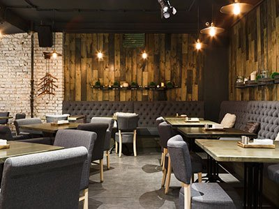 Small retail area inside a coffee shop with wooden walls, stone decor on a wall, gray floor, wooden tables, and dark gray couches.