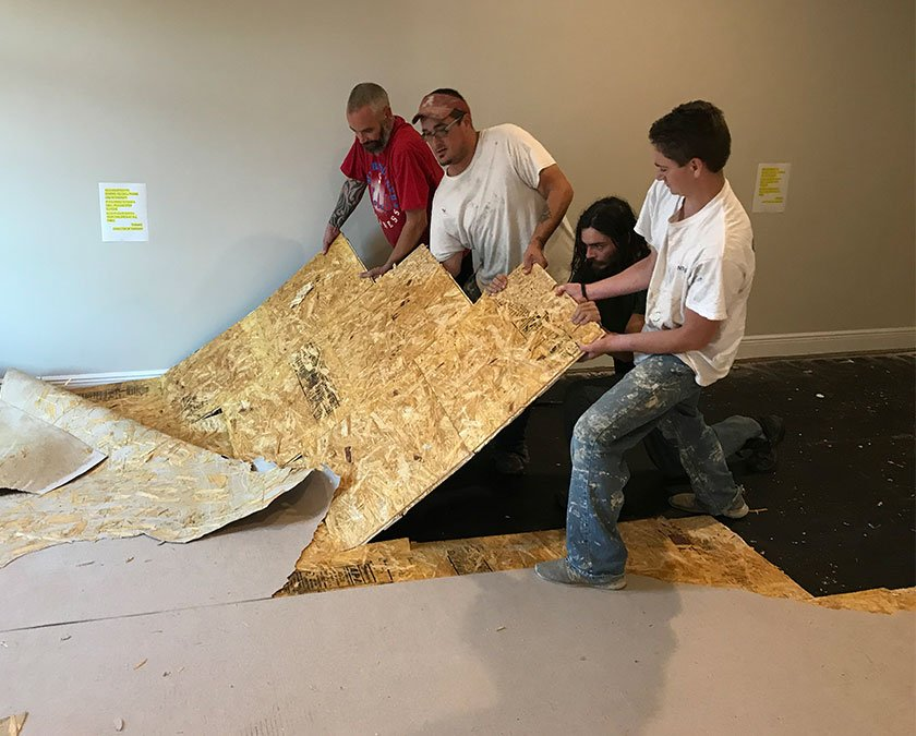 Team staff at work, tearing off the old floor.
