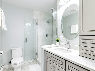 Guest bathroom with gray cabinets, marble floors, and big round mirror